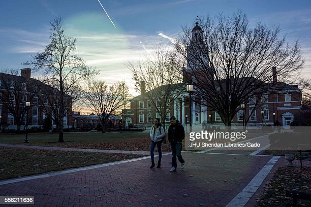 Two students walk on a brick path in front of Gilman Hall on the Keyser Quadrangle of the Homewood campus of the Johns Hopkins University in...
