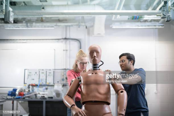 two students working on a test dummy in a workshop. - monty rakusen stock pictures, royalty-free photos & images