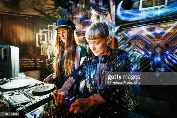 two stylish djs performing at colourful open air nightclub - dj stock pictures, royalty-free photos & images