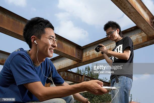 Two stylish young men listen to music and play video games while relaxing out on a barren, industrial looking urban rooftop.