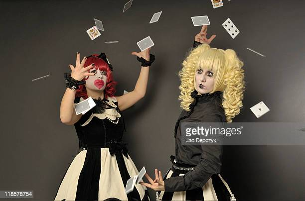 Two stylish young girls throwing playing cards