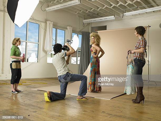 Two stylists watching as man photographs female model in photo studio