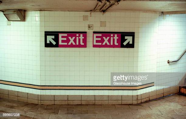 Two Subway Exit Signs Pointing in Opposite Directions
