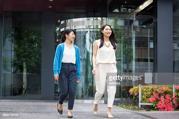 Two successful Japanese businesswomen walking together