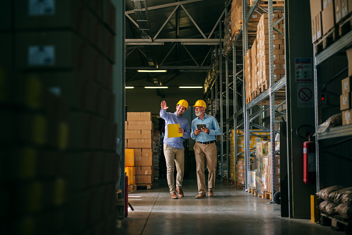 Two successful smiling business man walking through big warehouse with helmets on their heads.Younger man is shoving older one shelf's full of products ready to be delivered. Happy investors. 1049404210