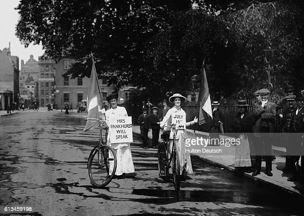 Two suffragettes on bicycles carry signs advertising a meeting where the militant campaigner Mrs Pankhurst will speak.