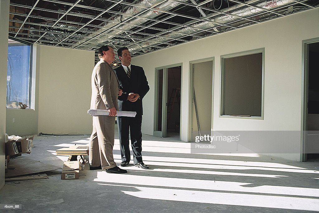 Two suited businessmen dressed in suits stand in an unfinished office talking : Stockfoto