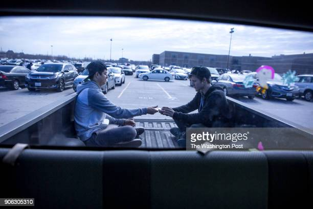 Two Summer Creek students wait out the parking lot traffic by practicing magic tricks in the bed of a pickup truck Left junior Daniel Berdeguez and...