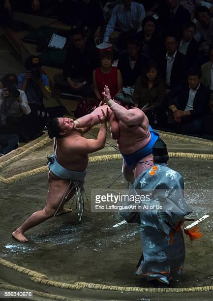 Two sumo wrestlers fighting at the ryogoku kokugikan arena kanto region tokyo Japan on May 20 2016 in Tokyo Japan