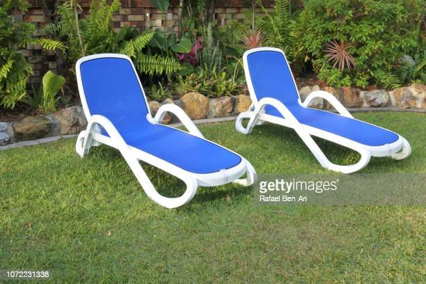 Two Sun Beds on a Green Grass