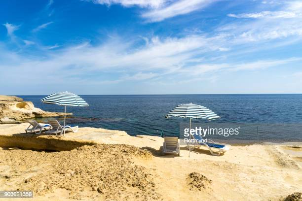 Two sun loungers with parasols on a beach