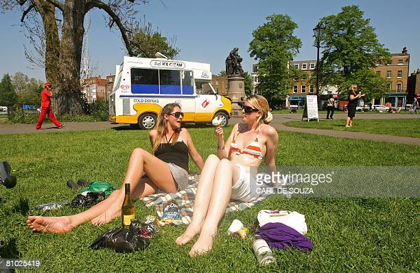 Two sunbathers enjoy the warm weather in Clapham Common in central London on May 08 2008 AFP PHOTO/CARL DE SOUZA