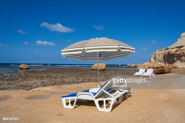 Two sunbeds and a beach umbrella next to the waterfront