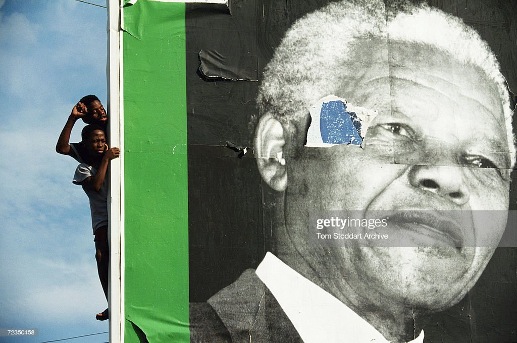 Two Supporters at an April 1994 ANC (African National Congress) rally in South Africa peer from behind a sign bearing the image of their President Nelson Mandela.