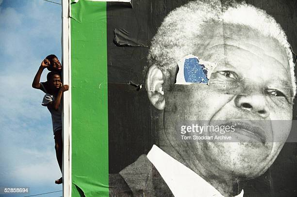 Two Supporters at ANC rally in South Africa peer from behind a sign bearing the image of their President Nelson Mandela