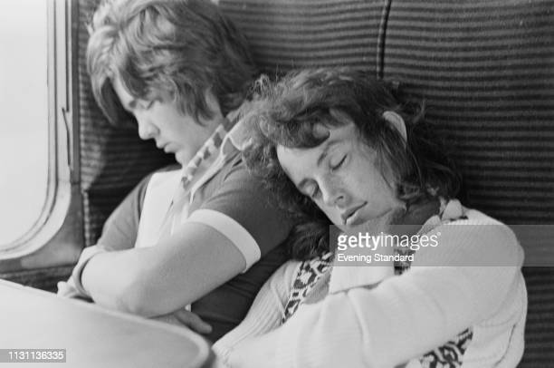 Two supporters of Millwall FC sleeping on a train, UK, 18th August 1975.