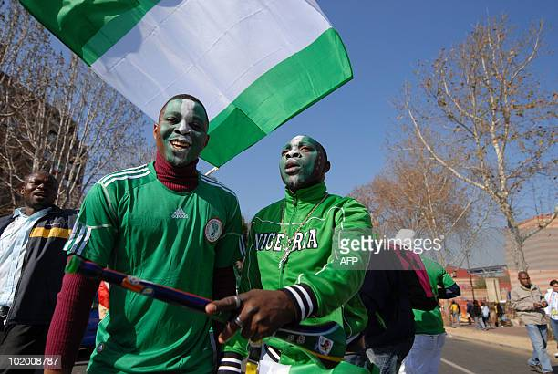 Two supporters of the Nigerian team one of them holding a Nigerian flag pose as they arrive for the 2010 Football World Cup match between Argentina...