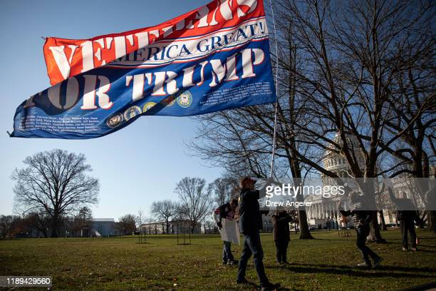 Two supporters of US President Donald Trump stand near protesters supporting the impeachment of US President Donald Trump gather outside the US...