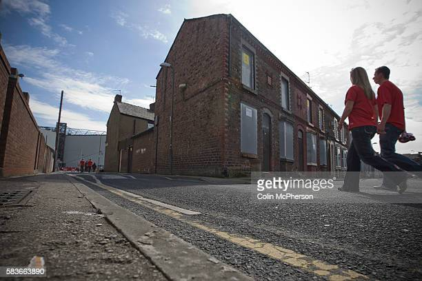 Two supporters walking past boarded up and derelict houses in a street adjacent to Anfield home of Liverpool football club pictured before the club...