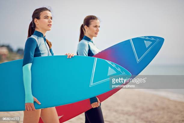 Two surfer girls are standing on the beach