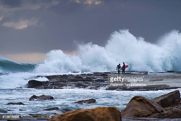 two surfer waiting to surfing with big wave - big wave surfing stock pictures, royalty-free photos & images