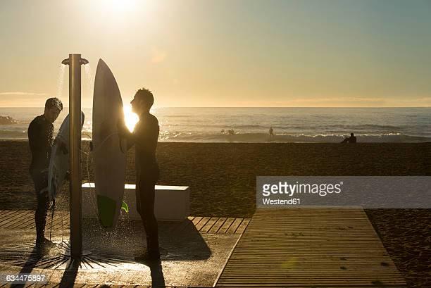 two surfers at sunrise on the beach, shower - maenner duschen stock-fotos und bilder