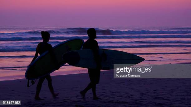 Two surfers carrying their boards at sunset on the beach Playa Carmen in Santa Teresa