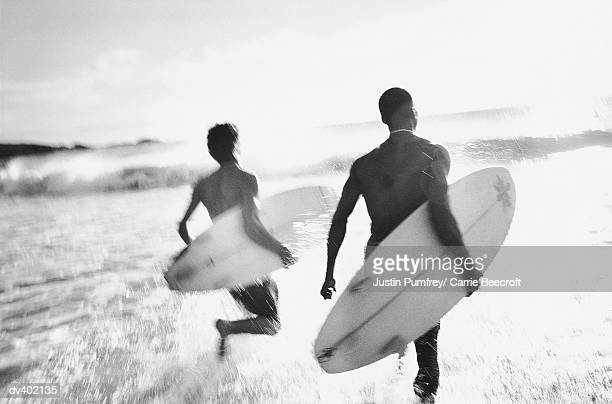 Two surfers heading out to waves