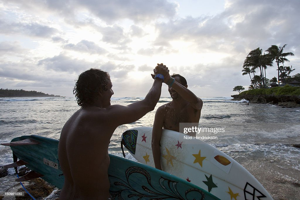 Two surfers high five on the beach : Stockfoto
