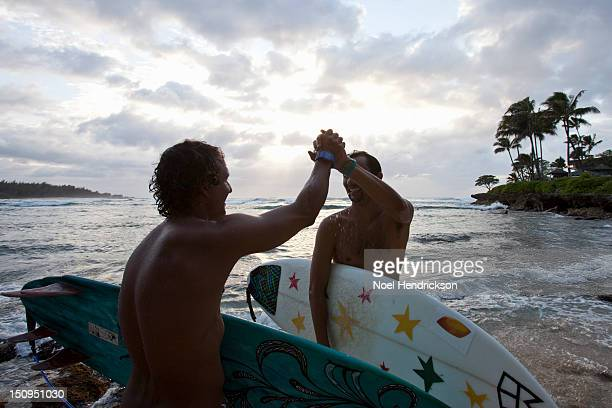 Two surfers high five on the beach