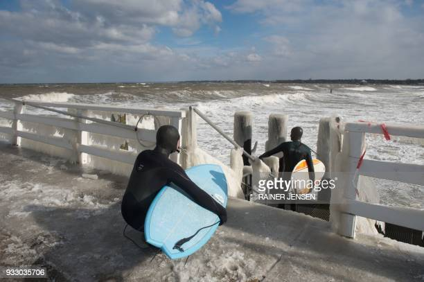 Two surfers in neoprene suits wait on icy stairs for a good wave as the Baltic Sea is lashed by the wind on March 17 2018 in Timmendorfer Strand...
