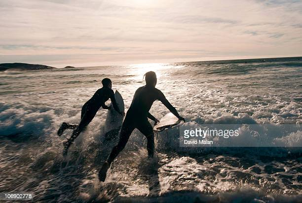 Two surfers leaping into the water at sunset.