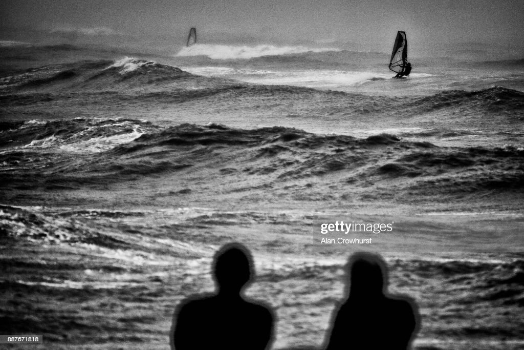 Two surfers look on as widsurfers and kitesurfers take advantage of the storm force winds off the coast of West Sussex on December 7, 2017 in Goring, England. Storm Caroline is expected to batter the UK with gusts of up to 90mph and poses a potential risk to life, according to the Met Office.