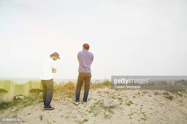 two surfers looking at the sea - yusuke nishizawa stock-fotos und bilder
