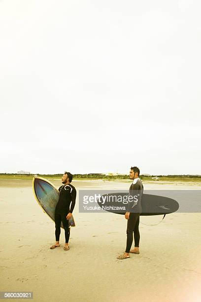two surfers looking at wavea