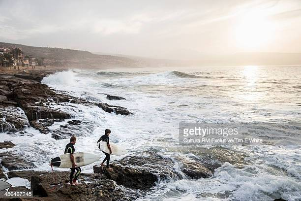 Two surfers on rocks at sunrise, Taghazout, Morocco