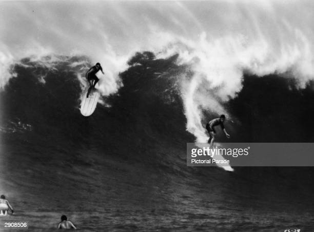 Two surfers ride a large wave in Waimea Bay Hawaii in a still from the international surfing documentary 'The Endless Summer' directed by Bruce Brown...