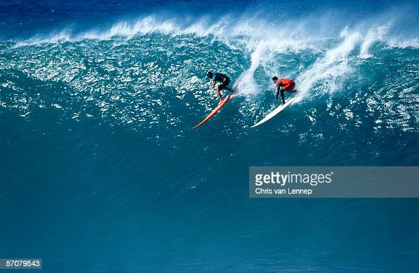 two surfers riding a huge wave - waimea bay hawaii stock photos and pictures