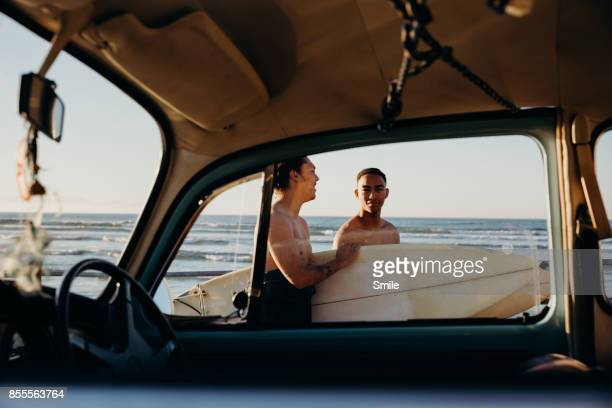 Two surfers seen through car window