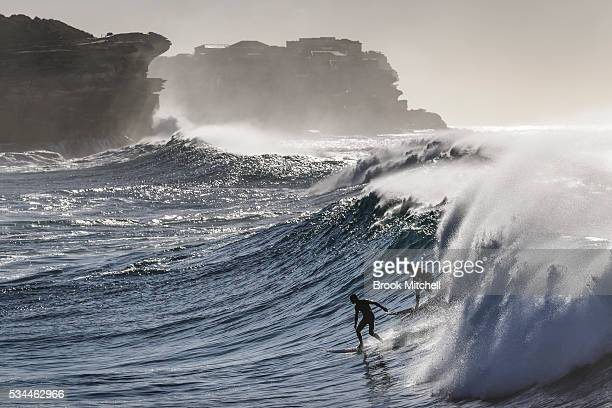 Two surfers share a wave at Bronte beach on May 25 2016 in Sydney Australia All Sydney beaches were closed to swimmers today as large waves pounded...