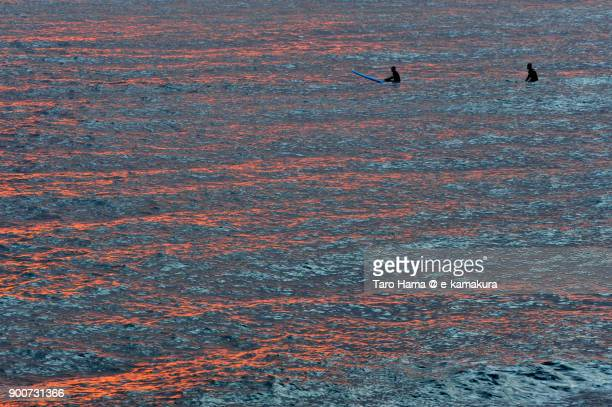 Two surfers waiting for next wave on the sunset beach in Kamakura city in Kanagawa prefecture in Japan