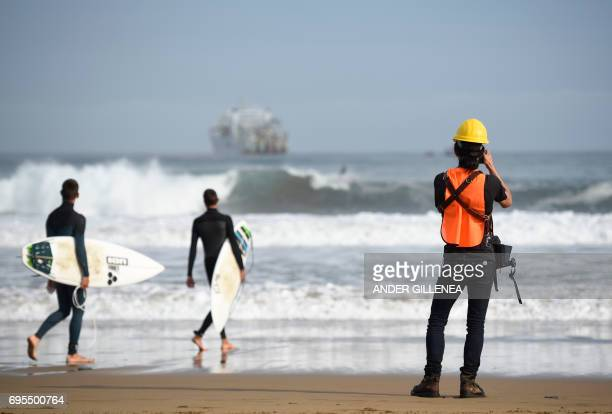 Two surfers walk into the water as an operator takes a picture during the mooring of an undersea fiber optic cable at Arrietara beach near the...