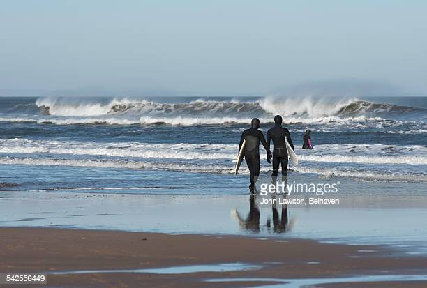 Two surfers walking towards the sea