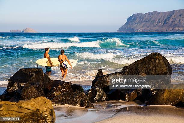 Two surfers with surfboards head out to ride teal waves on a sunny blue sky day in Kailua Hawaii on the Island of Oahu Rugged beautiful peninsula...