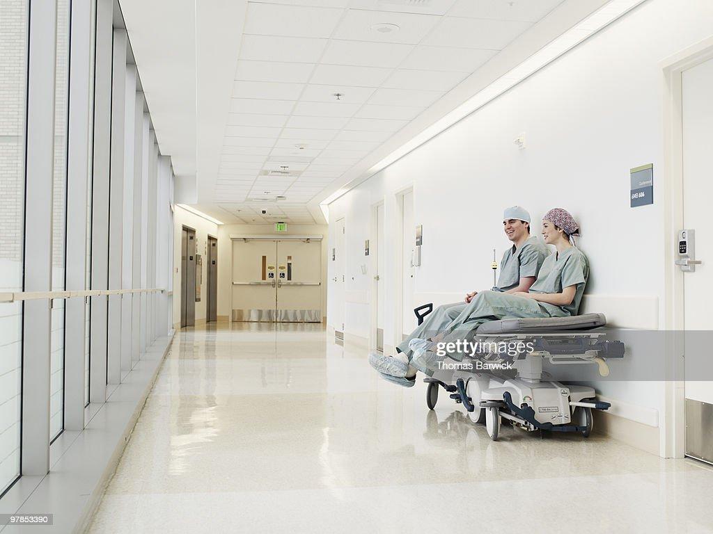 Two surgeons resting on gurney in hospital hallway : Stock Photo