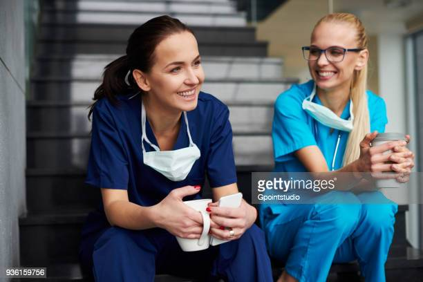 Two surgeons taking a break, sitting on steps, holding coffee cups, smiling