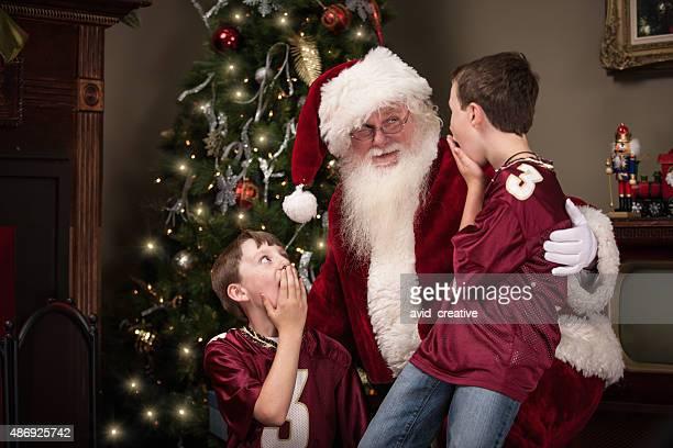 Dois rapazes sentados surpresa sobre o Pai Natal piscina na sala