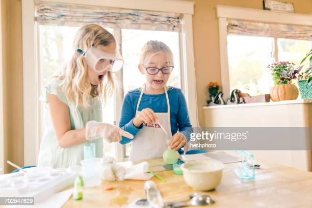 two surprised girls doing science experiment, pointing - heshphoto stockfoto's en -beelden