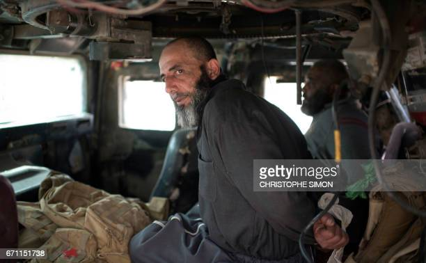 Two suspected men sit restrained in a Humvee, awaiting to be interogated on the front line in west Mosul on 21 April during the Iraqi forcecs'...