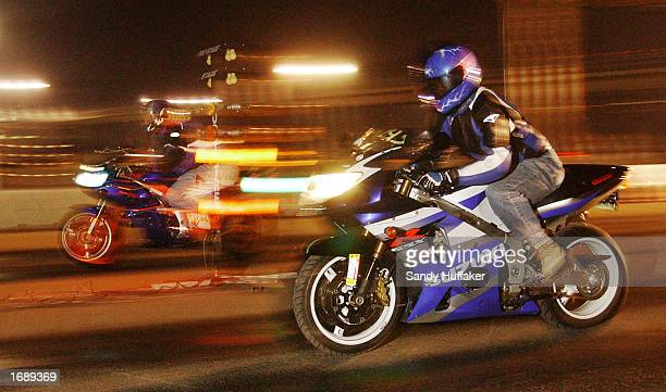 Two Suzuki Motorcycles burn rubber as they start a race at the RaceLegalcom drag race at Qualcomm Stadium December 13 2002 in San Diego California...